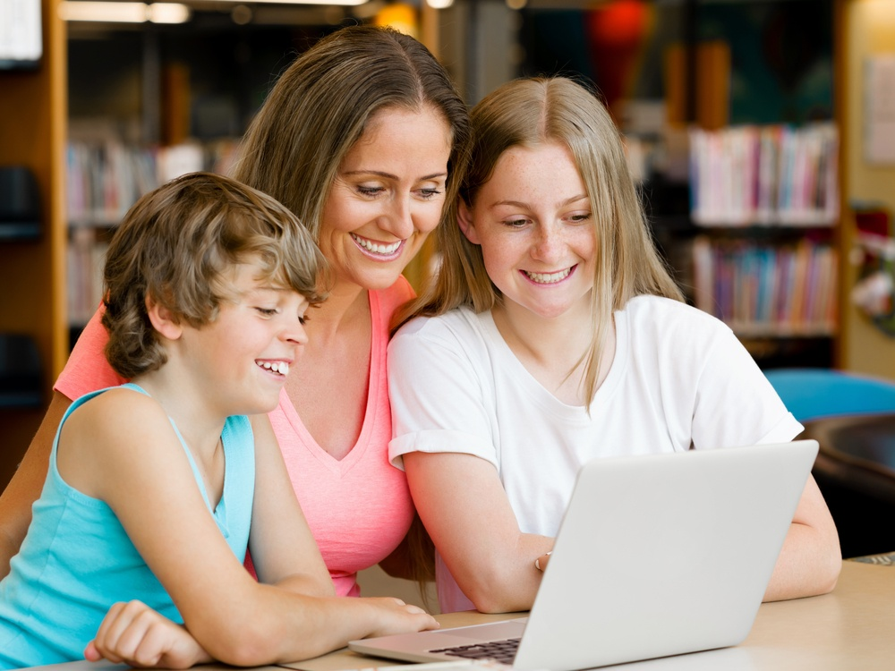 Mother with kids in library with notebook