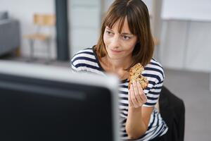 Office Woman Holding a Bread Snack While Working on her Computer at her Table.